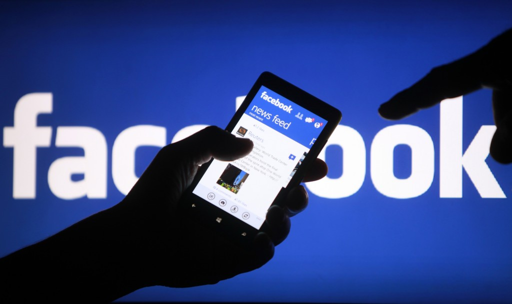 A smartphone user shows the Facebook application on his phone in the central Bosnian town of Zenica, in this photo illustration, May 2, 2013.  Facebook Inc's mobile advertising revenue growth gained momentum in the first three months of the year as the social network sold more ads to users on smartphones and tablets, partially offsetting higher spending which weighed on profits. REUTERS/Dado Ruvic (BOSNIA AND HERZEGOVINA - Tags: SOCIETY SCIENCE TECHNOLOGY BUSINESS)