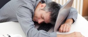 Image of a man sleeping at the working desk